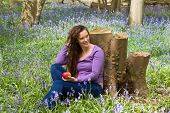 Relaxing young woman having an apple in a bluebells spring forest