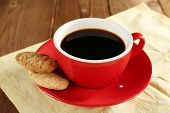 Cup of coffee on saucer with cookies on color napkin on wooden table background