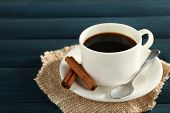 Cup of coffee with spoon and cinnamon on burlap cloth on color wooden background