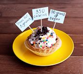 Delicious cake with calories count labels on color plate on wooden table background