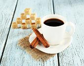 Cup of coffee on burlap cloth with coffee beans on color wooden background