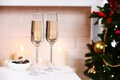 Two glass with champagne with bowl of chocolates on table on Fireplace background
