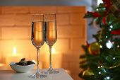 Two glass with champagne with bowl of chocolates on table on Christmas tree and fireplace with candles background