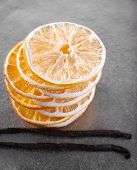 Pile of dried orange with vanilla beans on metal background