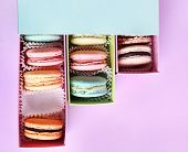 Assortment of gentle colorful macaroons in box on color background