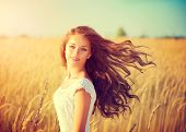 Beauty Girl Outdoors enjoying nature. Beautiful Teenage Model girl with long healthy blowing hair running on the Spring Field, Sun Light. Glow Sun. Free Happy Woman. Toned in warm colors