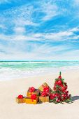 Christmas Tree And Gift Boxes On Sandy Beach