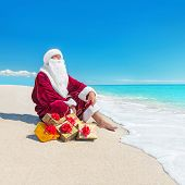 Santa Claus With Many Christmas Golden Gifts Relaxing At Tropical Beach