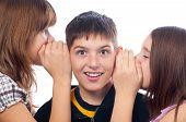 Two teenage girls telling secret to teenage boy