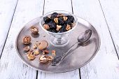 Metal tray with glass bowl of prunes and walnuts, shell and spoon on color wooden background