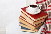 Pile of books with cup and plaid on the chair on brick wall background