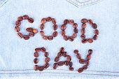 Sign Good Day made of coffee beans on jeans background