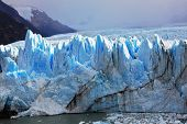 Huge Perito Moreno glacier in the Lake Argentino, surrounded by mountains.  Los Glaciares National Park in Patagonia. Sunny summer day