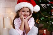Little girl in Santa hat sitting near fir tree on fireplace with candles background