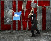 Businessman Holding Hammer Hitting Red Limit Word On Concrete Wall