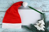 Santa red hat with fir-tree branch, card and pencil on color wooden background