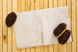 picture of pastarelle  - Mini eclairs on a wooden background with a sheet of paper for information - JPG