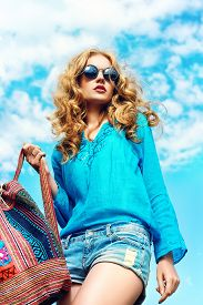 image of hair motion  - Gorgeous young woman with beautiful wavy hair wearing casual blouse and jeans shorts posing outdoor - JPG