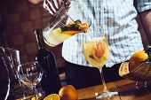 image of sangria  - Man pours white homemade sangria with fruit pieces in a glass - JPG