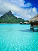 pic of french polynesia  - Luxury overwater honeymoon bungalows in a vacation resort in the clear blue lagoon with a view on Mt - JPG