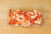 stock photo of fantail  - Fantail prawns in a plastic carton on a wooden board - JPG