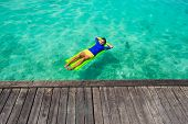 picture of mattress  - Young  man swimming on an inflatable mattress in the clear sea - JPG