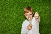 pic of inhalant  - Portrait of a boy breathing through inhaler mask over spring green grass background - JPG