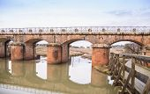 stock photo of oasis  - Bridge made by red bricks that pass through the canal of a natural oasis in Tuscany - JPG