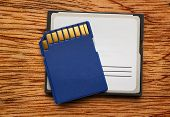 picture of memory stick  - Blue compact memory cards for camera on wooden background - JPG