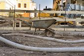 stock photo of hand-barrow  - Construction site with old barrow and tubes - JPG