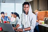 foto of programmers  - Black programmer in lounge of IT start - JPG