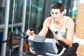 picture of cardio  - young man at cardio training on bicycle machine station in fitness gym - JPG