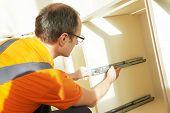 image of carpenter  - Craftsman kitchen carpenter at kitchen cabinet installation service work - JPG