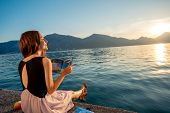 picture of sea-scape  - Young woman reading book and looking at beautiful sunrise on the pier with sea and mountains on background - JPG