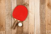 foto of ping pong  - Ping pong paddle and ball on vintage wooden background - JPG