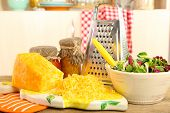 pic of grating  - Grated cheese on wooden table in kitchen - JPG