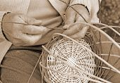Постер, плакат: Expert Hands Of The Elderly Craftsman Creates A Woven Wicker Basket
