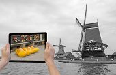 stock photo of monochromatic  - In the bottom left of the photo are hands holding tablet whose screen contains color photo of the yellow clogs - JPG