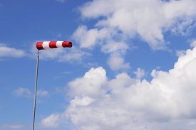 image of wind vanes  - Image of a red white wind vane against blue sky with white clouds - JPG