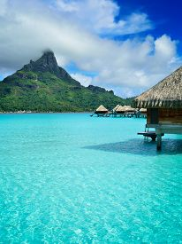 image of french polynesia  - Luxury overwater honeymoon bungalows in a vacation resort in the clear blue lagoon with a view on Mt - JPG