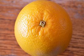 pic of valencia-orange  - Closeup of Valencia orange on a wood table  - JPG