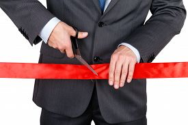 stock photo of pompous  - Businessman in suit cutting red ribbon with pair of scissors isolated on white background - JPG