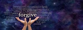 pic of forgiveness  - Female open palm hands on a panoramic deep space dark blue background reaching up to the word Forgive above surrounded by a relevant word cloud and copy space on right side - JPG