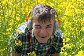 pic of rape-field  - Teenager with headphones on the rape field  - JPG