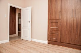 stock photo of laminate  - Bedroom of New House with build in cupboards and laminated floor as viewed towards the open door to the bedroom - JPG