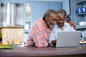 Smiling couple using laptop computer in kitchen at home poster