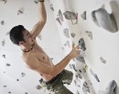 foto of climbing wall  - young and fit man exercise free mountain climbing on indoor practice wall - JPG