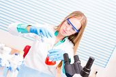 A female lab assistant doing scientific experiments in a scientific laboratory poster