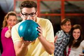 Group of four friends in a bowling alley having fun, three of them cheering the one in charge to thr