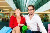 kuppelkirche Mann und Frau in einem Einkaufszentrum mit bunten Taschen; Sie haben eine Pause